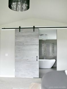 An open shot of modern gray barn door (with @NationalHrdware) to reveal the stunning bathroom of @TarynAtDDD of Design, Dining and Diapers