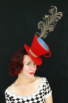 Red felt Mad Hatter tea cup hat in a tilt topper style.  Liquid beverage made of wrinkled iridescent blue shimmery fabric, and the steam is made from a single long curled white peacock feather.