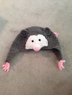 Crocheted hat with ear flaps. It has Opossum feet on each flap and a tail on the back. It can be made in infant, toddler, or child size. A bow can