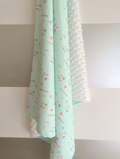 This mint and gold minky baby blanket features sweet little vintage florals - perfect for a retro, whimsical nursery. But this blanket isnt all
