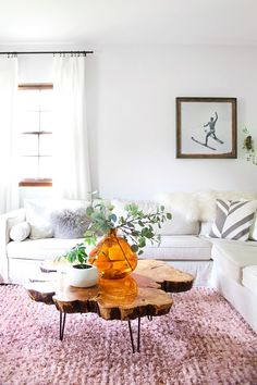 Feminine living room with a white sectional, a pink rug, and a wood coffee table