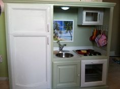 this is a childs play kitchen made from an old entertsinment center..i think this is an awesome idea!