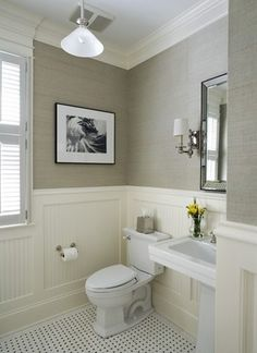 Backer Board Wainscoting with Square Frames, Crown Molding, Elaborate Window Casing, Window Shutters, Square Pedestal Sink, Brushed Nickel Framed Square Mirror.  Maybe Install Ceiling Light Fixture and use Similar Artwork
