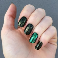 glittering olive and emerald green manicure // Main: China Glaze Zombie Zest, over black. Accent nail: Nfu-Oh flakie polish, over black