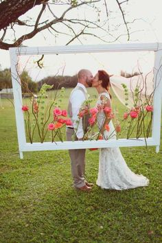 Crisp white picture frame filled with pink and orange flowers and greenery, created by Passion Roots, Hawaii Wedding Florist. www.passionroots.com: