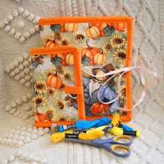 Love the autumn with its pumpkin fields and dancing scarecrows? Then this sewing organizer set is for you! The armchair caddy and needle book are both made from cotton fabric with a cheerful design of pumpkin fields, scarecrows and sunflowers. They are lined with off white broadcloth and reinforced with fusible batting. The edges are finished with bright orange bias tape. Both pieces are designed to be folded up when theyre not in use, making them perfect for carrying your handwork projects…