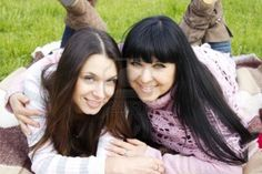 Portrait of smiling mother and teenage daughter hugging in the park happy Stock Photo
