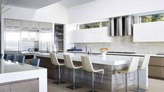 This massive kitchen, which boasts gray cabinetry and millwork, serves as the hub of this Palm Beach home.