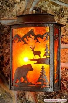 A wildlife scene crafted from metal is illuminated  from behind in the hand-  crafted wall sconce pictured .
