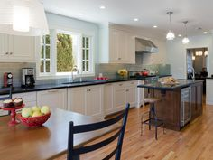 This well-crafted transitional kitchen does its part with a center island for prep work, a beverage center to keep the kids out of the cooking area and lots of counter space. Blue subway tiles add a dash of color that complements the dark countertops.