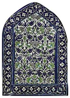 A LARGE DAMASCUS POTTERY TILE PANEL   OTTOMAN SYRIA, 17TH CENTURY   Of arched form, with finely drawn lattice of cobalt-blue tulips and hyacinths, green and manganese carnations and green and turquoise blue split palmettes, bordered by a band of floral arabesques reserved on cobalt-blue ground, in wooden frame, repaired breaks, areas of repainting