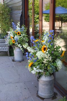 Milk churns outside the Ceremony Barn at Upwaltham by Rose Cottage Flowers