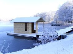 Floating sauna with a traditional gabled roof.