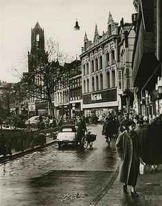 De Oudegracht 1956: Nabij de Bakkerbrug. Krap hoor, winkelen op zo'n smal stoepje.....ze rijden je zo voor je sokken!