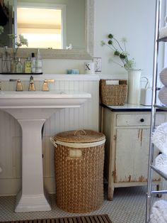 Lovely white bathroom - ceramics softened and warmed by the use of hand made basketry and a shabby chic cupbaord