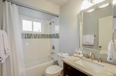 Grandview Bathroom renovation by Dwelling Studio with white subway tile, soaking tub, new toilet, vanity, and fixtures.