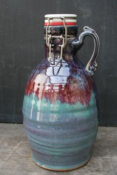 When a potter brews beer, its only logical that handthrown growlers follow.  This growler is handthrown on the wheel out of white stoneware, glazed inside and out, then fired in a gas kiln to create a very durable and vibrant vessel. This is our patina glaze- a recipe of my own creation. The ceramic flip-top lid is made by Portland Growler Co, and is replaceable. I have two growlers that are very similar, and are therefor both under this listing, Ive added one picture of both to show the…