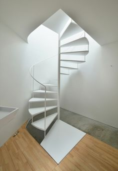white spiral staircase with a slender handrail winds through each of these apartments from an entrance hall and bathroom at ground level, to a living area on the first floor and a mezzanine bedroom sitting below the sloping roof. Spiral Stairs Design, Staircase Design, Staircase Ideas, Modern Staircase, Mezzanine Bedroom, Steel Cladding, Casa Loft, Stair Steps, Roof Architecture