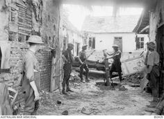 A medium trench mortar and crew of the 3rd Australian Medium Trench Mortar Battery, 2nd Division, in action in a farmhouse 400 yards from the German front lines. Gun position selected and made use of to support Infantry raid prior to attack on Morlancourt village. Left to right: Lieutenant J. Arthur; Lt L. C. Reeves; Gunner (Gnr) W. Commons, holding cleaning rod; Gnr G. Parker, loading mortar; Corporal P. Barber. 29th May, 1918
