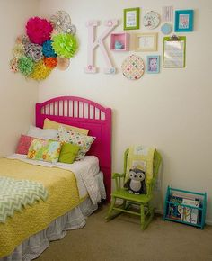 Such a cute, colorful little girls room! Love the use of tissue paper flowers on the wall!