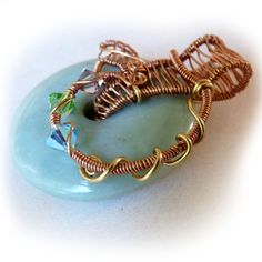 Simple and beautiful. This lovely, light teal gemstone donut (I pretty sure it's amazonite) is wrapped in flowing copper and bronze. The bail is hand woven. The feel of the piece is of waves on a foamy blue-green sea.  Wire wrapped donut gemstone, teal, copper, bronze&crystal