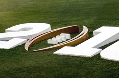 The fabricated aluminum channel logo is stake mounted to the ground. The highly custom angled construction creates a seamless rise from the grass.