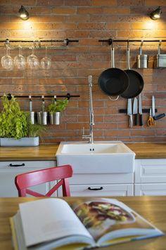 W kuchni na ścianie z cegieł przymocowano uchwyty na akcesoria i zioła w…
