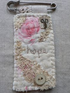 Absolutely gorgeous little brooches (and needlebooks and more) - but I especially love this one with its mixture of handmade stitches and refined lace, watercolor look image, vintage button, and more - just perfect! - via gentlework: February 2013