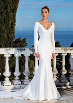 All eyes will be on you in this crepe long sleeve gown. It features a pearl seam detail down the sleeves, along the wrists and at the neckline. A clean V-back with pearl buttons down the train create this stunning wedding day look.