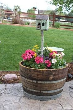 Barrel pot with flowers and bird house---will take the bird house made out of our barn wood with me to my new home.