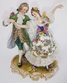 Antique Dresden German Volkstedt Dancing Couple Porcelain Figurine is in very fine vintage condition for its age. The woman and man are dressed exquisitely and both have the beautiful lace found on Dresden pieces.