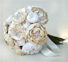 Silk Catala and Jeweled Bloom bouquet is comprised of hand cut and formed silk fabric flowers of various shades of cream and ivory.  Each flower has its own hand placed highlights featuring either rhinestones, crystals, or genuine freshwater pearls.