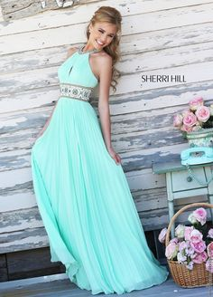 New for 2015...Richly textured, the A-line silhouette of Sherri Hill 11251 prom dress vows to charm beginning with its ruched bodice that cradles an elongated keyhole stretching from the beaded halter neckline down to the more grandiose beadwork hugging the midriff. From there, the electric pleated skirt cascades freely down the floor where it settles with a brush train. Also available in White-Gold, Light Green, Light Blue and Black-Multi.