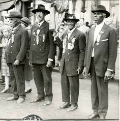 """The last remaining Grand Army of the Republic members pose in suits with medals and ribbons. These Black (African American) Civil War veterans include (L to R) John Ayers, William Rochester, George Harris, and William Johnston."""