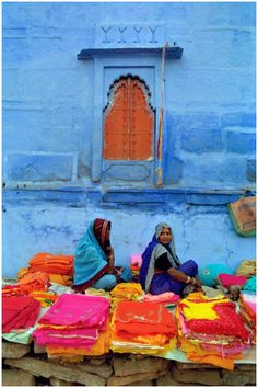 INDIA:  Sari sellers against a sky blue wall - Daily life in Rajasthan