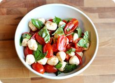2 pints cherry or grape tomatoes, quartered  1/2 teaspoon sugar  Salt and pepper  1 tablespoon balsamic vinegar  1 garlic clove, minced  2 tablespoons extra-virgin olive oil  8 ounces fresh mozzarella cheese, cut into 1/2-inch cubes and patted dry  1 cup chopped fresh basil