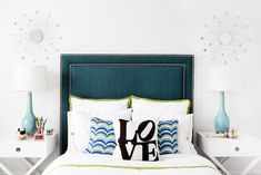 Chic teen girl's bedroom boasts a peacock blue headboard with brass nailhead trim on full bed dressed in white and green bedding, blue and green pillows and a black and white LOVE pillow flanked by white x based nightstands, Williams-Sonoma Home Hudson Side Tables, topped with robin's egg blue table lamps situated under small silver sunburst mirrors.