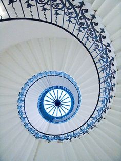 symmetrical clean white spiral staircase. black iron railing. up to the ceiling. natural lighting.