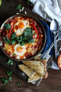 Smokey Mexican Baked Eggs - olive oil, chorizo, brown onion, garlic clove, baked paprika, chili flakes, tomato, Mexican salsa/canned diced tomatoes, capsicum, canned corn (would use frozen or omit), salt & pepper, eggs, cheese & coriander (to garnish), toasted bread (to serve, would omit)