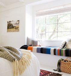 In this bright, white room, colorful stripes provide a bold accent on this window seat for lazy afternoon lounging.