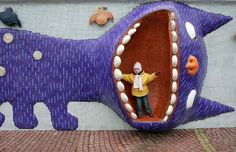 A girl stands in the mouth of a cat sculpture in central Kiev, Ukraine Picture: REUTERS