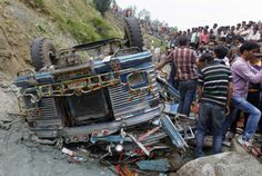 People gather near the wreckage of a bus carrying school children after an accident in Nambalnar, 55 km (34 miles) north of Srinagar, July 11, 2012.