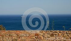 Photo taken near Malaga in Spain. The simple but evocative image contains essentially four elements, a low wall in the first floor, built with pieces of rock, the deep blue color of the sea, the sky blue and a ship off.