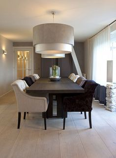 Modern luxury #dining area with large light fixture. We love the large wood panelled floors!