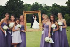 Cute shot of the bridesmaids holding an open-back photo frame and the couple positioned inside the frame.