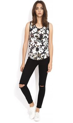 Trance Tank by WISH has a scooped neckline with thick straps. The women's top has a relaxed fit, falling down to approximately the hipline with a straight hem. Comes in a black and white floral print with a plain black back.