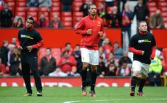 Manchester United's English defender Rio Ferdinand (C), not wearing an anti-racism Kick It Out T-shirt, warms-up next to Brazilian midfielder Anderson (L) and English forward Wayne Rooney (R) before their team's English Premier League football match against Stoke at Old Trafford in Manchester, north-west England on October 20, 2012