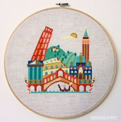 This modern cross stitch pattern of Italy features the Leaning Tower, the Colosseum, the Pantheon, St Marks Basilica, the Piazza San Marco tower,