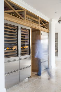 Project: Ashurst House | Kitchen Design: Nickleby | The Nickleby design embodies the true spirit of the classic contemporary kitchen. | This is the walk in larder with Sub-Zero wine preservation units and refrigerator drawers to the left, and the solid oak wine racks above. #humphreymunson #subzero #refridgerator #wine #storage #oak #larder #ideas #bespoke #inspiration