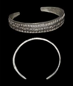 9th-11th century AD. A Viking period silver bracelet, cast as a flat-section bar; c-shaped in plan; the surface ornamented with borders of triangle punchmarks and a medial band of pellet-in-triangle punchmarks; the ends narrow, squared and slightly thickened. Silver, 32.4 grams, 76 mm. Extremely fine condition.